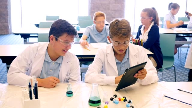 Male high school STEM students prepare for chemistry experiment