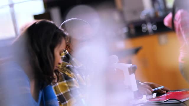 vídeos de stock, filmes e b-roll de a male high school student chats while his lab partner takes notes. - aluna da escola secundária