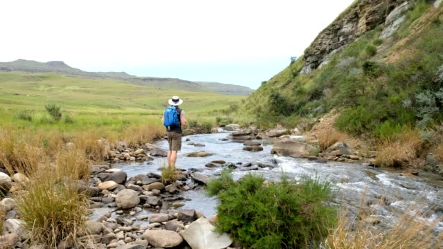 Male hiker admires the river flowing through the valley