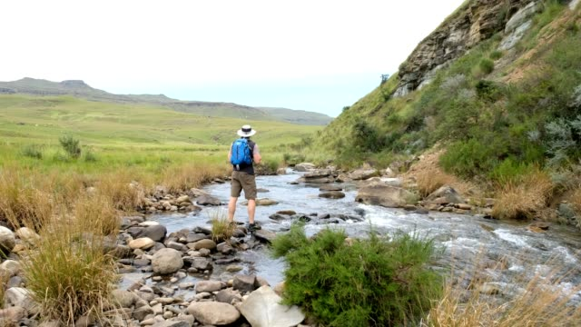 male hiker admires the river flowing through the valley - drakensberg mountain range stock videos & royalty-free footage
