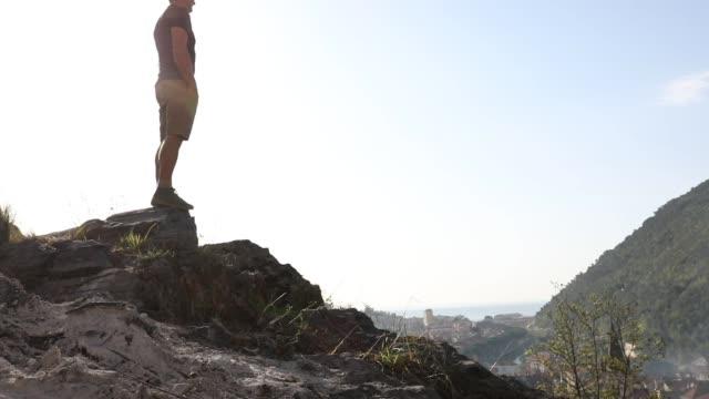 Male hiker ascends dusty slope at sunrise