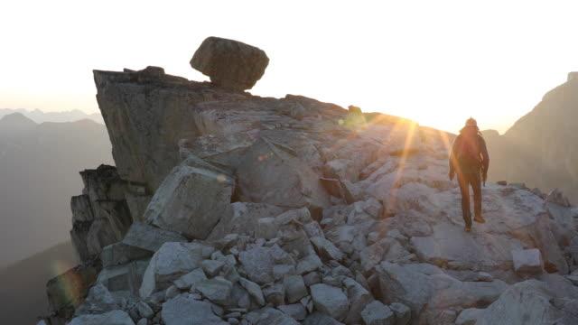 male hiker ascends mountain ridge at sunrise - mountain ridge stock videos & royalty-free footage