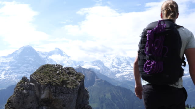male hiker ascends rock buttress above valley, mountains - t shirt stock-videos und b-roll-filmmaterial
