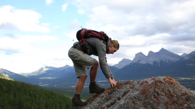 Male hiker ascends rock pinnacle, looks out across mountains and forest