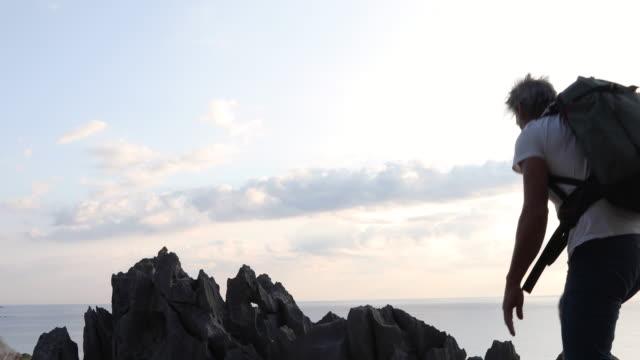 männlicher wanderer steigt bei sonnenaufgang auf felsrücken - t shirt stock-videos und b-roll-filmmaterial