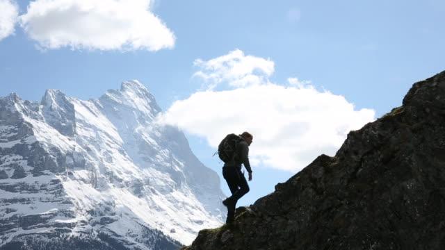 Male hiker ascends rock ridge, looks towards snow capped peaks