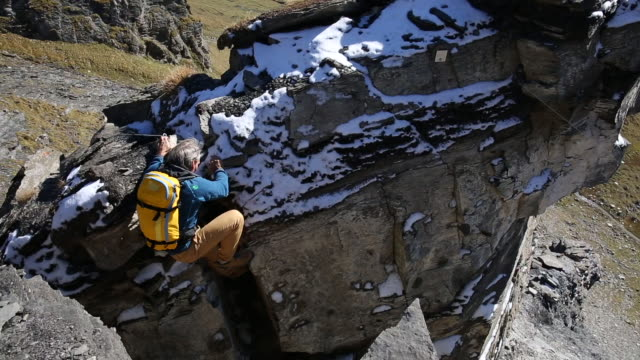 Male hiker ascends snow covered rock pinnacle, valley below