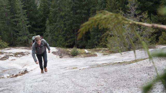 Male hiker ascends steep granite slab through forest