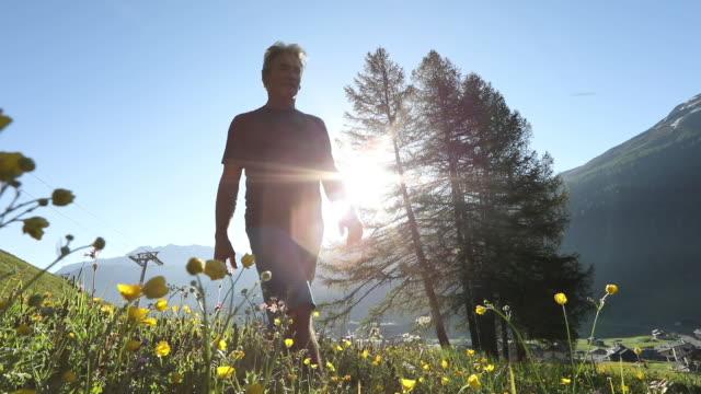 vídeos y material grabado en eventos de stock de hombre excursionista asciende a través de prado alpino al amanecer - one mature man only