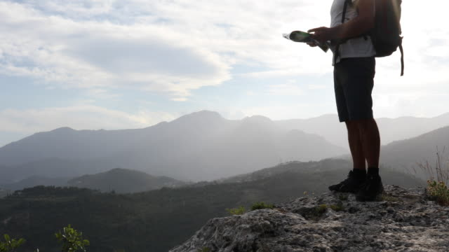 male hiker ascends to rocky perch above valley - road map stock videos & royalty-free footage