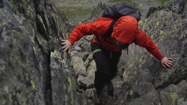 vídeos y material grabado en eventos de stock de caminante masculino subiendo por un sendero rocoso en una montaña - riesgo