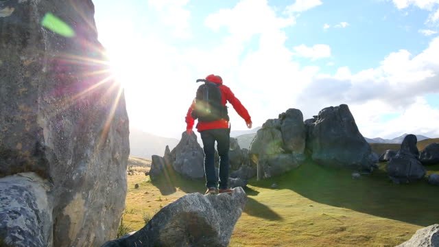 male hiker climbs boulder above rock field at sunrise - boulder rock stock-videos und b-roll-filmmaterial