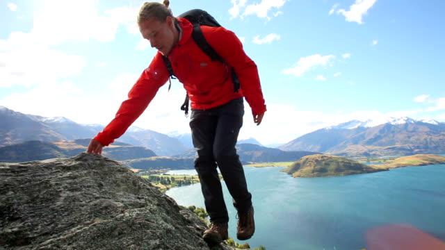 vídeos de stock, filmes e b-roll de male hiker climbs rock bluff above lake and mountains - coque cabelo para cima