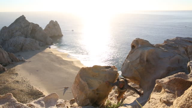 Male hiker climbs through rocks above beach, sunrise
