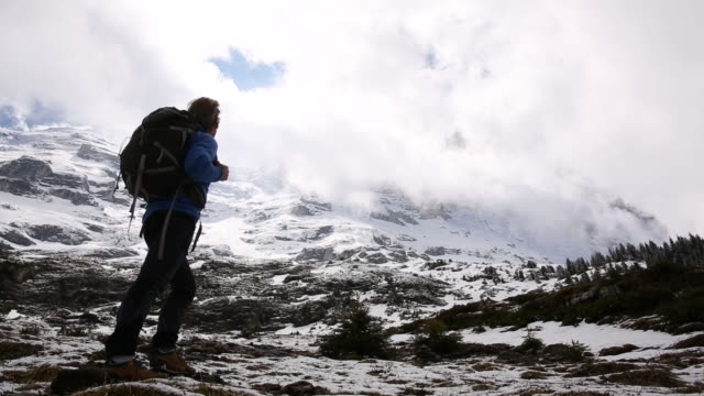 male hiker climbs through snowy meadow below snow capped mountains - scalare video stock e b–roll