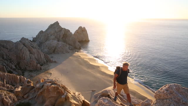Male hiker climbs to crest above beach, sunrise