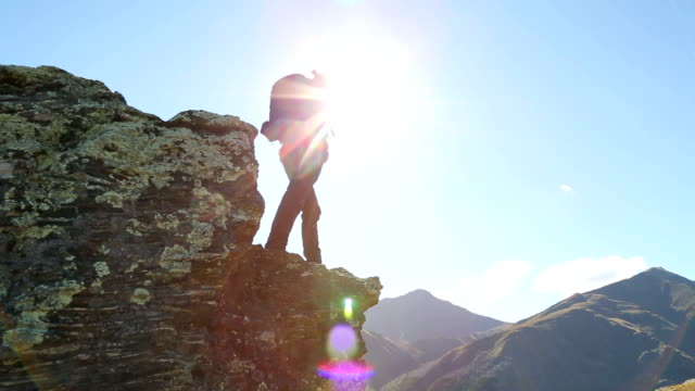 male hiker climbs to mountain summit above lake - adventure stock videos & royalty-free footage