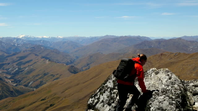 male hiker climbs to mountain summit above mountain range - top garment stock videos & royalty-free footage