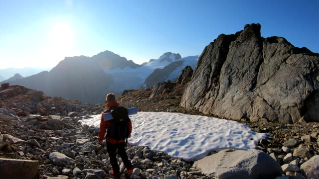 male hiker descends mountain slope at sunrise - moving down stock videos & royalty-free footage
