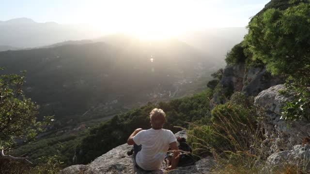 stockvideo's en b-roll-footage met male hiker descends to rocky perch above valley - leunen