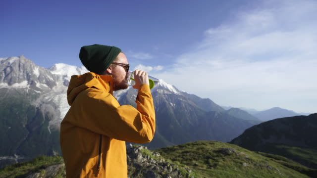 vídeos de stock e filmes b-roll de male hiker drinks from water bottle in mountains - casaco curto com mangas