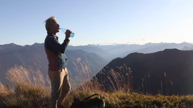 vídeos y material grabado en eventos de stock de el senderismo masculino bebe agua en la cresta alpina al amanecer - agua potable