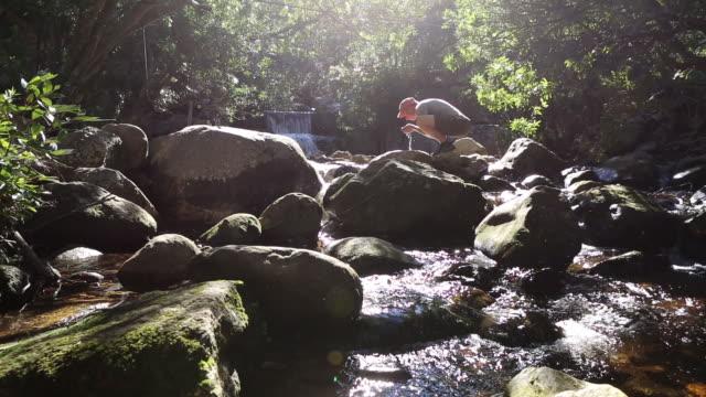 vidéos et rushes de randonneur mâle profiter de l'eau douce des rivières - torrent