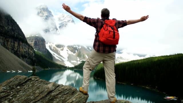 male hiker enjoying success viewing lake moraine canada - red lake stock videos & royalty-free footage