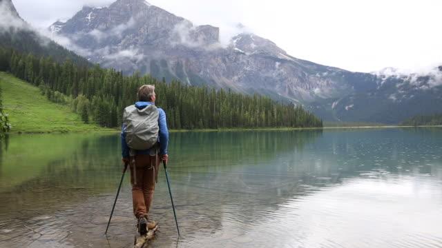 Male hiker explores mountain lake shoreline after rainstorm