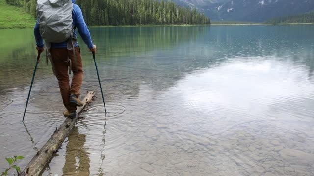Male hiker explores mountain lake shoreline during rainstorm