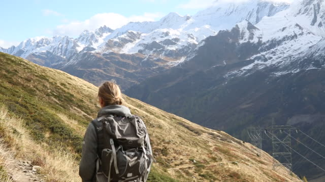 Male hiker follows pathway across mountain slope, snowy mtns