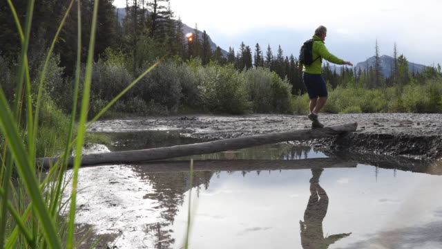 male hiker follows shoreline pathway across creek - awe stock videos & royalty-free footage