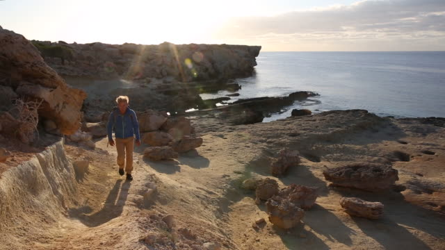 male hiker follows trail beside tidal rocks, at sunrise - republic of cyprus stock videos & royalty-free footage