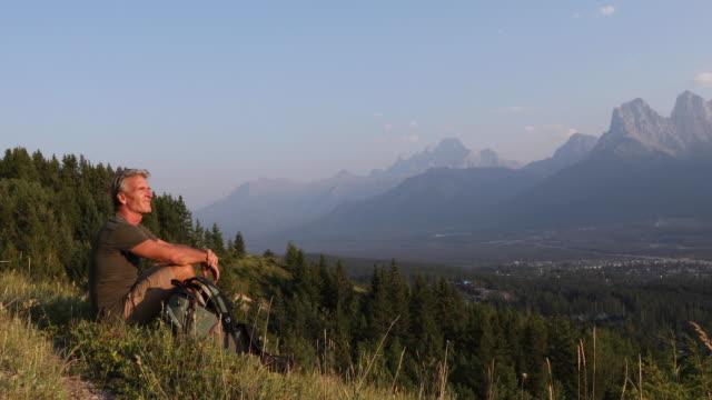 male hiker follows trail on meadow ridge crest, sunrise - mature men stock videos & royalty-free footage