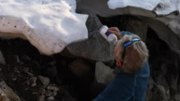 Male hiker gathers water from melting snowpack