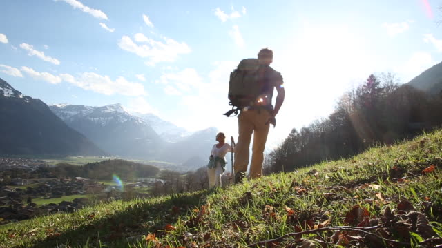 male hiker joins woman on mountain slope, drops pack - cinquantenne video stock e b–roll