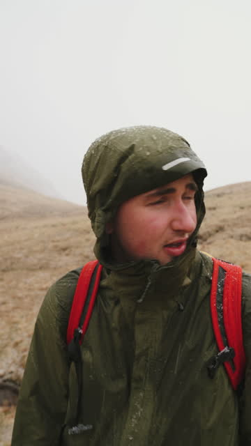 male hiker looks off during sleet/ rain storm - less than 10 seconds stock videos & royalty-free footage