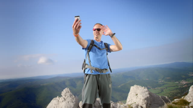 male hiker on a video call on mountain top - pointing stock videos and b-roll footage