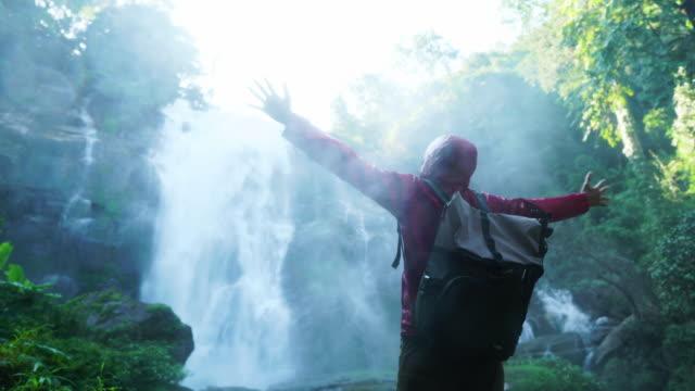 滝の前で手を伸ばす男性ハイカー - バッグ点の映像素材/bロール