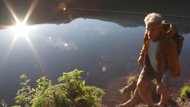 male hiker pauses at lake edge, sunrise - at the edge of stock videos & royalty-free footage
