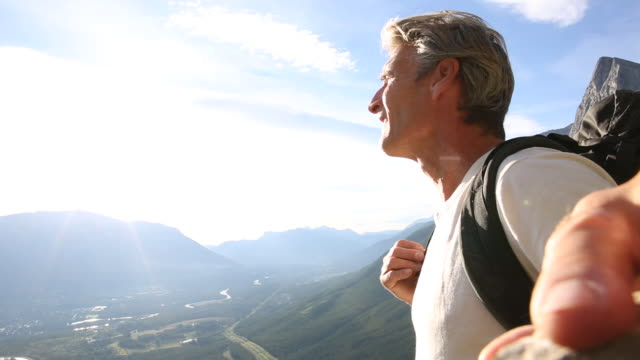 male hiker pauses, looks off to mountains and valley - shirt stock videos & royalty-free footage