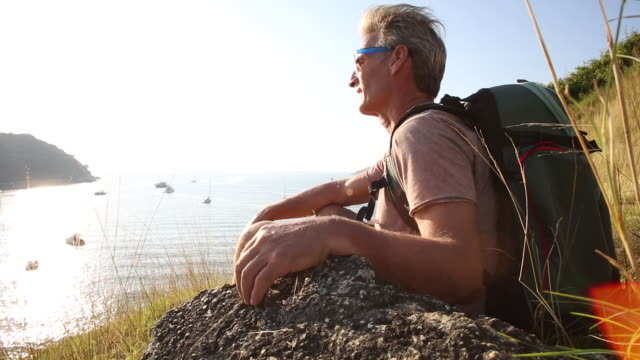 Male hiker pauses on grass ridge crest, looks out over sea