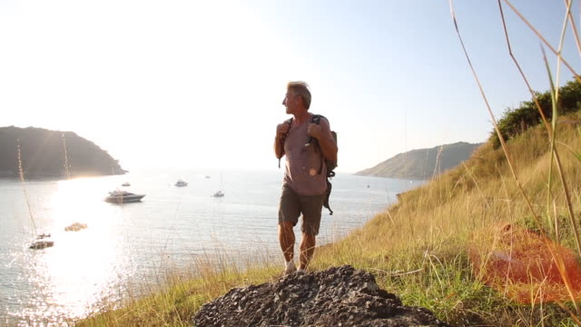 male hiker pauses on grass ridge crest, looks out over sea - phuket stock videos & royalty-free footage