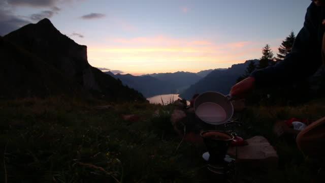 männliche wanderer bereitet mahlzeit über seen und bergen bei sonnenaufgang - nur junge männer stock-videos und b-roll-filmmaterial