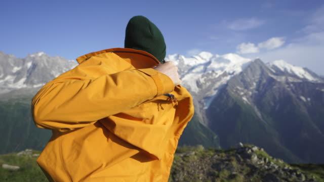 vidéos et rushes de le randonneur mâle met sur la veste dans le paysage alpin - manteau et veste