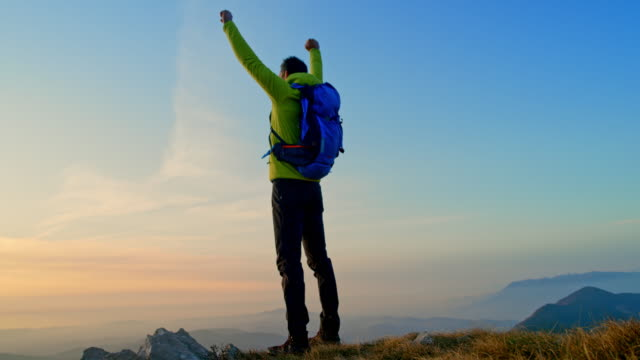 slo mo male hiker raising his hands in victory as he reaches the top of the mountain at sunset - opportunity stock videos & royalty-free footage