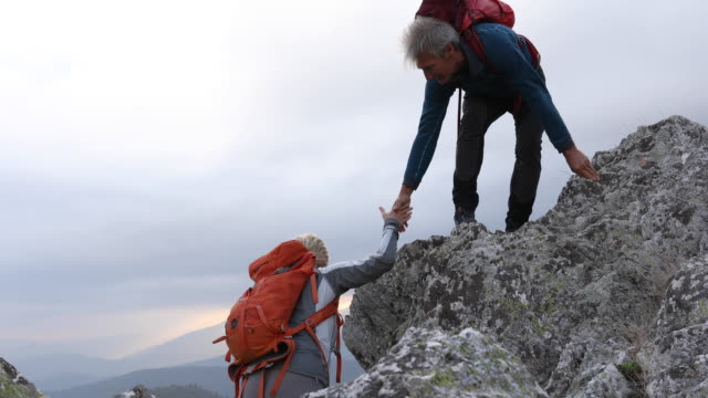 vídeos de stock e filmes b-roll de male hiker reaches hand down to female companion - 55 59 anos