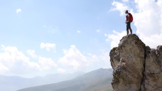 vídeos de stock e filmes b-roll de male hiker reaches pinnacle summit, above valley - risco