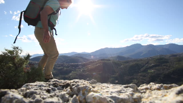 Male hiker reaches rock crest above hills, looks off