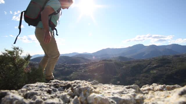 男性ハイカー オフに見える丘の上の岩稜に達すると